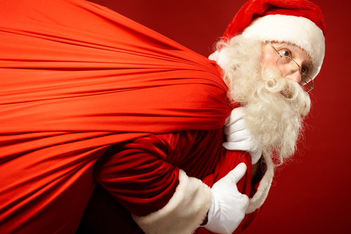 Portrait of Santa Claus carrying huge red sack with presents
