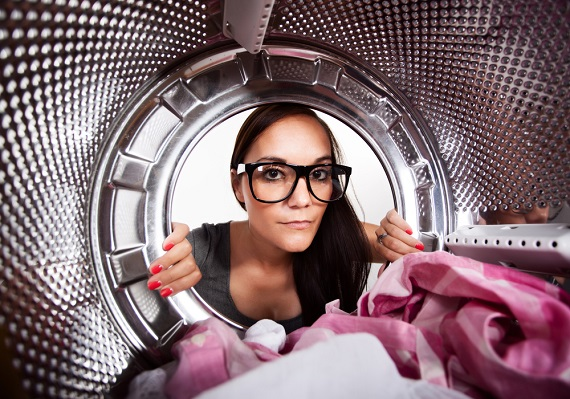 woman looking into a cloehtes dryer
