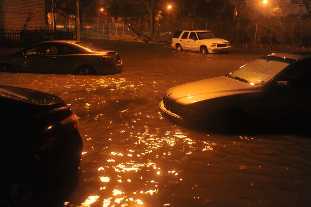 flood damaged cars partially submerged on a street