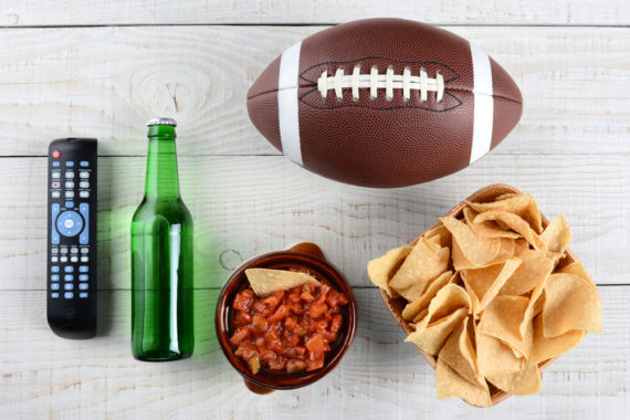 Super Bowl party ingredients: snacks, beer, a football and a remote