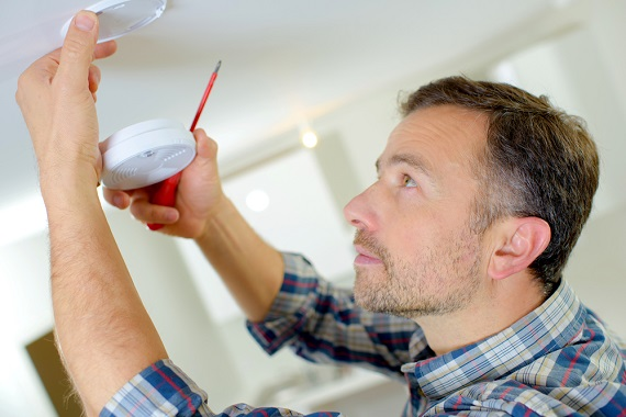 man changing smoke detector for spring home maintenance