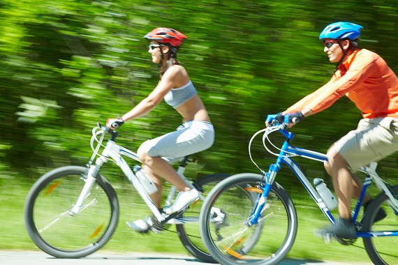 man and woman riding bikes, wearing bike helmets