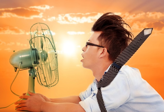 man sitting in front of fan with hair blowing