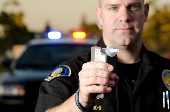 DUI check - policeman holding a breathalyzer