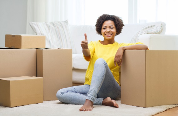 happy woman with boxes at a new aparment