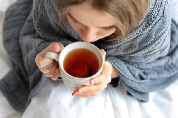 Woman with flu bunlded in blankets, sipping a hot beverage