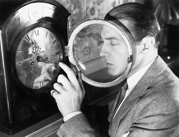 old time film image of a man setting a clock