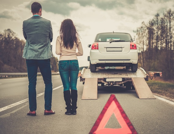 couple watching their car loaded on a tow truck