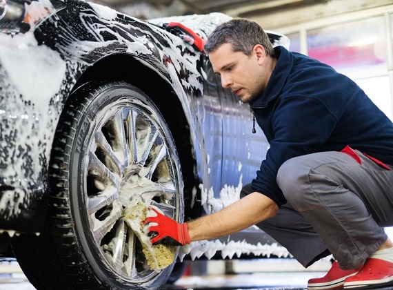car maintenance - man washing the tires