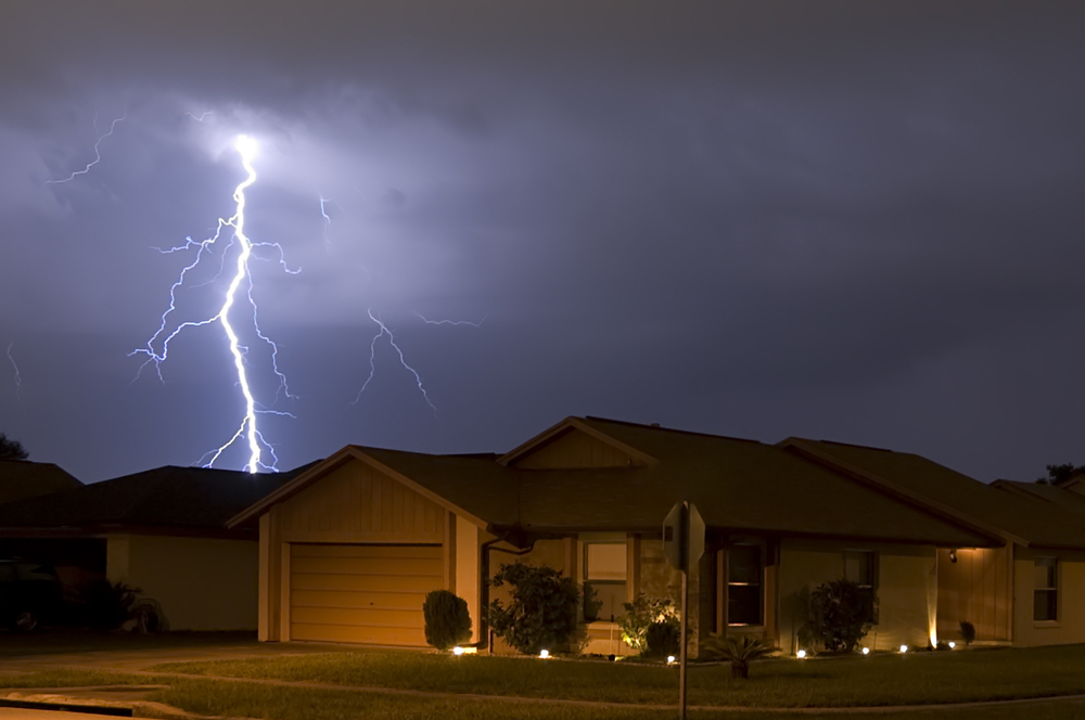 lightning strike at night, home in foreground