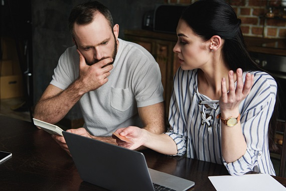 worried couple checking credit reports on computer
