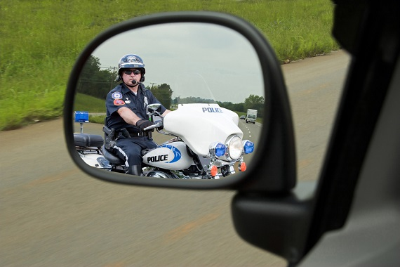 traffic tickets - cop on a motorcycle seen through a driver's car mirror