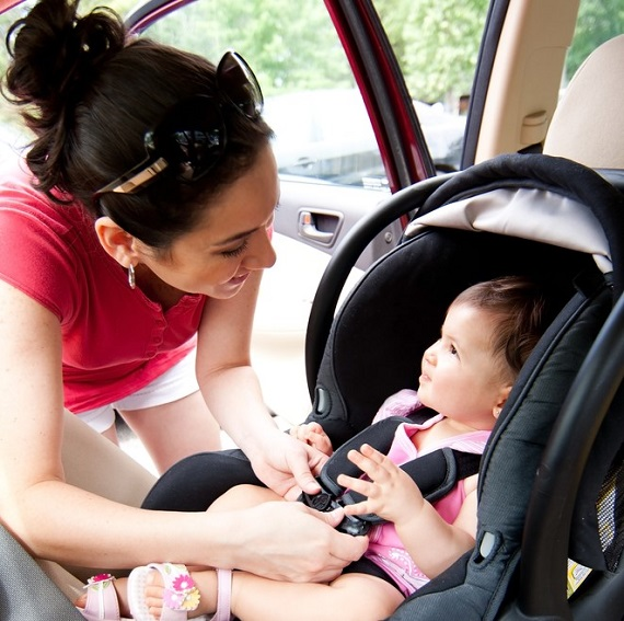 mother buckling a smiling baby in a child car safety seat